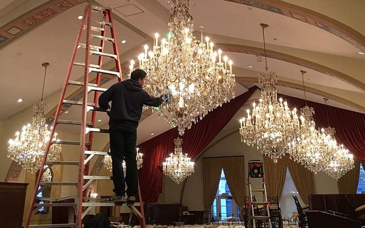 man standing on ladders and cleans chandalier